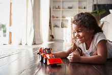 Young Hispanic Girl Lying On The Floor In The Sitting Room Playing With A Toy Digger Truck