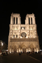 facade of the Notre Dame cathedral in Paris by night with some tourists