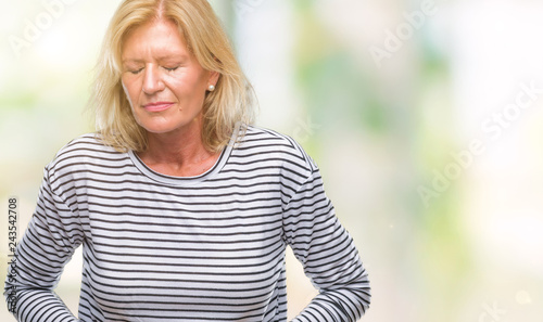 Fotografia  Middle age blonde woman over isolated background with hand on stomach because indigestion, painful illness feeling unwell
