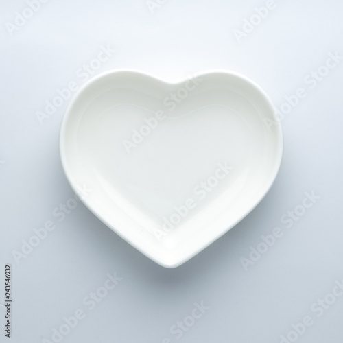 Minimalism. Empty plate in the shape of a heart on a white background in the center of the frame. Modern ceramic glossy dishes. Concept of Valentine's Day or wedding romantic theme. Square. Copyspace.