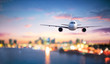 canvas print picture - Airplane In Flight At Twilight With Blurred Cityscape