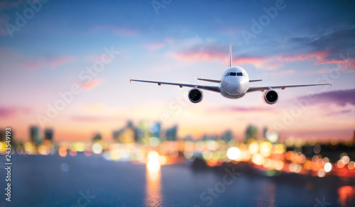Poster Avion à Moteur Airplane In Flight At Twilight With Blurred Cityscape