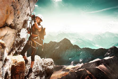 Fotografie, Obraz  Girl climbing on a Via Ferrata