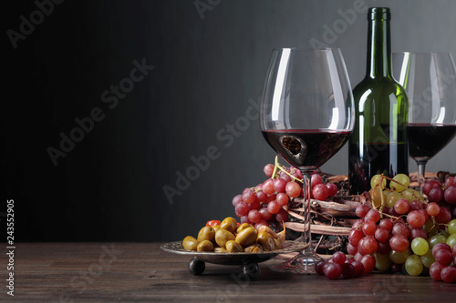 Red wine with spicy green olives and grapes.