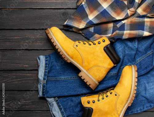 Fotografía  Men's casual wear, yellow work boots from natural nubuck leather, blue jeans, checkered shirt and brown belt on dark wooden background top view flat lay copy space
