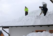 Zwei Männer Schaufeln Schweren Schnee Von Einem Hausdach. Gefahr Auf Dem Hausdach Im Winter Durch Zu Schweren Schnee