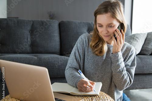 Focused freelancer writing down customer instructions Canvas Print