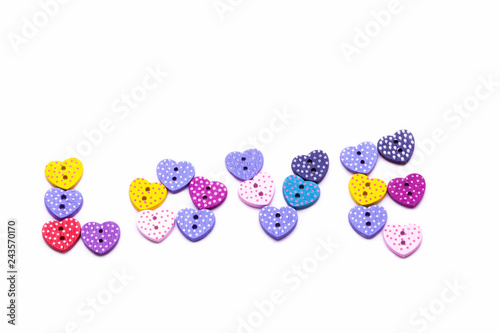 the word LOVE spelled out with colorful heart shaped buttons