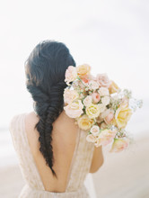 Rear View Of Bride With Bouquet On Beach