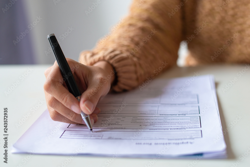Fototapeta Close-up of lady filling application form. Unrecognizable woman in sweater sitting at table and preparing her resume. Job search concept