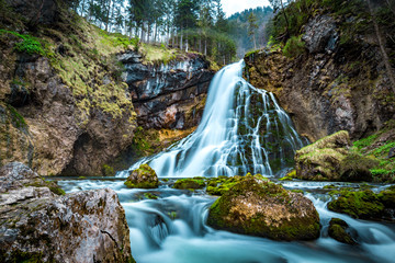 Idyllic waterfall scene with mossy rocks in the forest