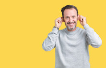 Handsome Middle Age Senior Man Wearing A Sweatshirt Over Isolated Background Smiling Pulling Ears With Fingers, Funny Gesture. Audition Problem