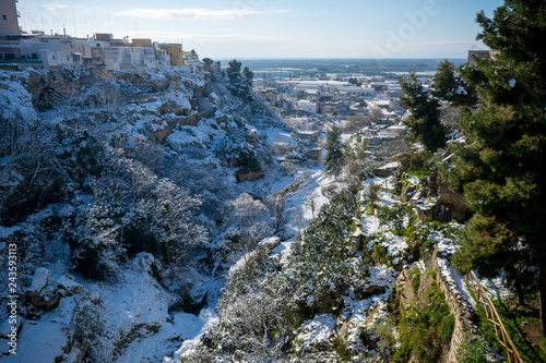 Valokuva  Horizontal View of the Gravina of the Town of Massafra, Covered by Snow on Blue