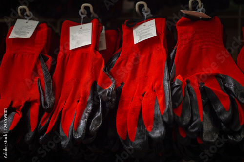 Fotografija  red construction gloves on the shelf in the hardware store