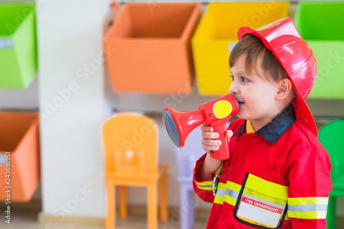 Obraz na płótnie Caucasian boy kid dress up to fireman and use speaker at roll play classroom,Kindergarten preschool education concept