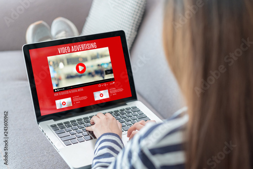 Shoulder view of woman watching video online with advertising on laptop computer on sofa at home.viral influencer media concept.