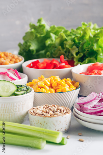 Fotografie, Obraz  Assortment ingredients for healthy vegetarian salad in different portion bowls on a table