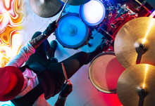 Drummer Playing On Drum Set On Stage In The Color Light. View From Above