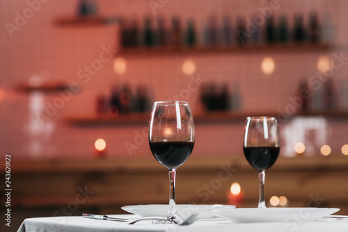 Foto op Canvas Alcohol Two glasses with red wine on a served table in a restaurant close-up. Romantic atmosphere, blurred background