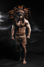 American Indian Apache Warrior Chief  In Traditional Clothing And Feathered Headdress With Weapon. Indian Chieftain Of The Tribe With Muscled Strength Body On Smoke Dark Background.
