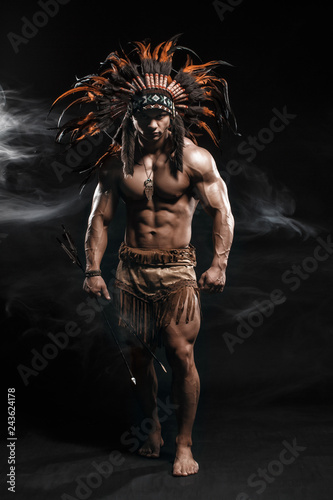 American Indian Apache warrior chief  in traditional clothing and feathered headdress with weapon Canvas Print