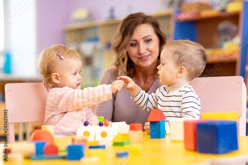 Nursery teacher looking after children in nursery. Little kids toddlers girl and boy play together with toys.