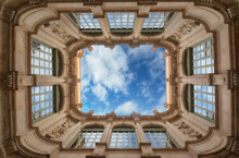 Bottom Wide Angle View Of Historic Inner Courtyard With Beautiful Facade Building Complex With Blue Sky And Clouds And Reflection In Windows In Barcelona, Spain. Geometric Shape