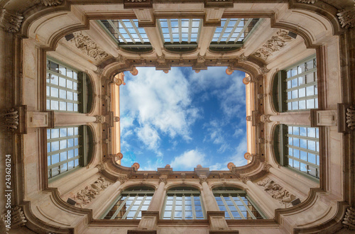 Bottom wide angle view of historic inner courtyard with beautiful facade building complex with blue sky and clouds and reflection in windows in Barcelona, Spain Fototapeta