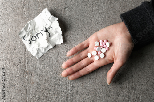 Female hand with pills and death note with word SORRY on grey background Tablou Canvas