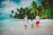 family with child walking on tropical beach
