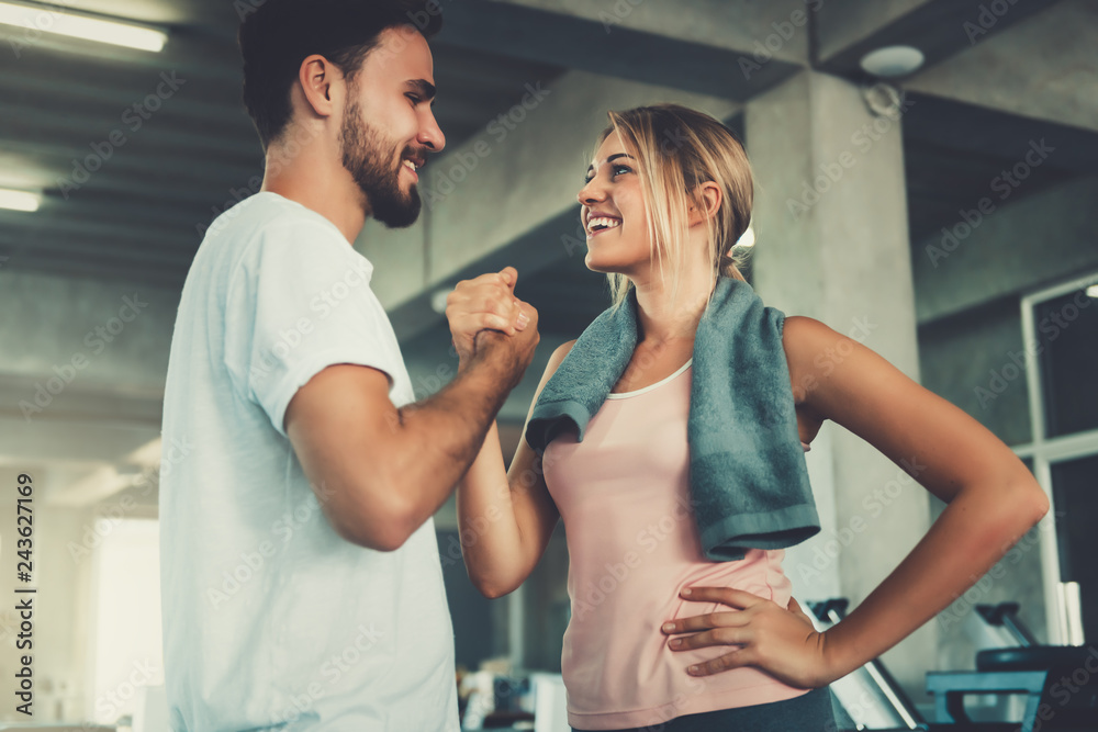 Fototapety, obrazy: Attractive young couple handshaking after workout in fitness gym., Portrait of man and woman couple love are working out training together., Couple fitness and healthy concept.