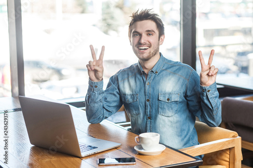 Fotografie, Tablou  Portrait of handsome successfull positive bearded young freelancer in blue jeans shirt are sitting in cafe and working on laptop with toothy smile and showing victory sign, looking at camera