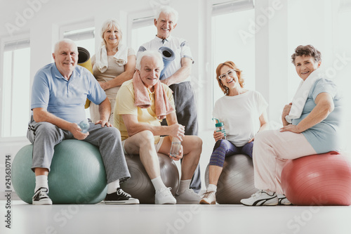 Group of active seniors sitting on exercising balls in modern fitness center after sport's training
