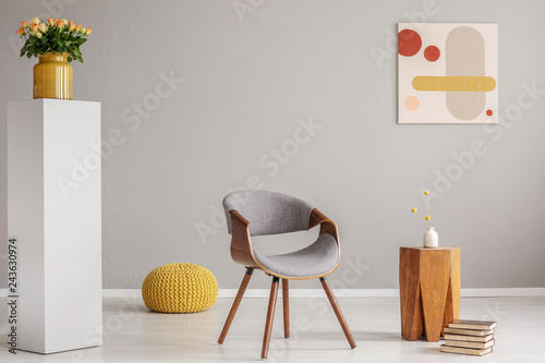 Fotografía  Pile of books next to wooden coffee table with flower in vase and trendy grey ch