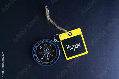Photo  PURPOSE inscription written on wooden tag and compass on black background with selective focus and crop fragment
