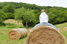 Girl Playing Sitting On A Bale Of Hay In A Meadow