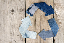 Recycle Symbol Made From Denim Fabric Over Wooden Background