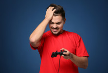 Young Man After Losing Video Game On Color Background