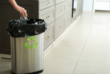 Young Woman Throwing Empty Plastic Bottle Into Trash Bin At Home. Recycle Concept