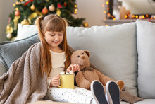 Cute Little Girl Drinking Hot Chocolate At Home On Christmas Eve
