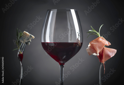 Glass of red wine with blue cheese, rosemary and prosciutto.