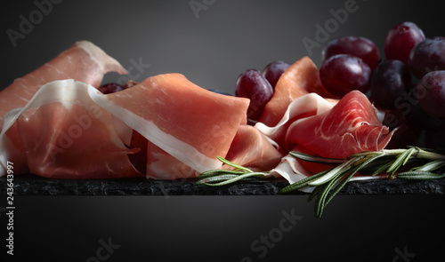 Prosciutto with grapes and rosemary .