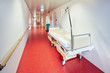 canvas print picture - Krankenhaus mit Korridor und Bett und mit Arzt unscharf in Zentralperspektive rot