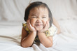 cute little asian girl toddler smiling on bed. concept of happiness, childhood and lifestyle