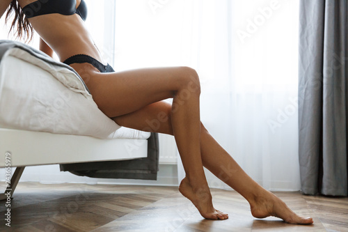 obraz lub plakat Beautiful amazing brunette woman wearing lingerie in home indoors sitting on bed.