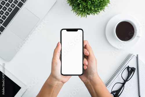 Foto  Hand using smartphone on white wooden background