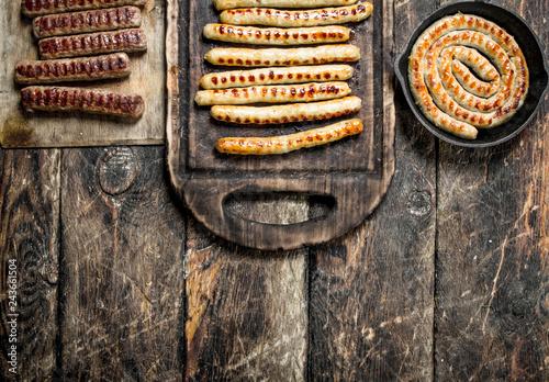 Fotografie, Obraz  Grilled sausages. On wooden background.