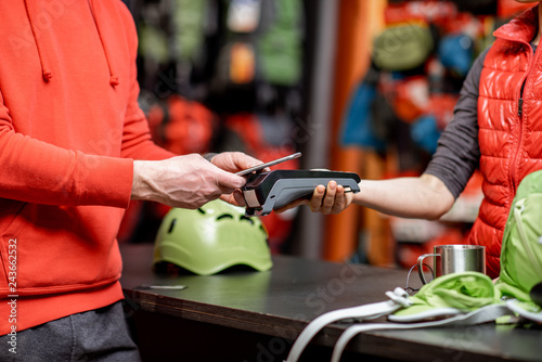 Man making purchase with smart phone and cash register at the counter of the sports shop