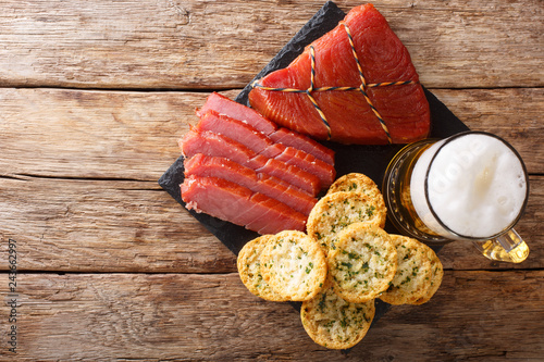 Light beer with foam, smoked tuna and toast with garlic and greens closeup. horizontal top view