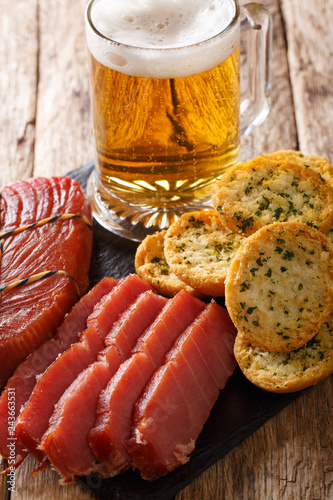 Light beer with foam, smoked tuna and toast with garlic and greens closeup. vertical